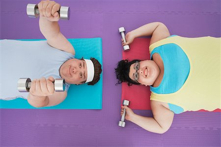 fat man exercising - Overweight man and woman lying down lifting dumbbells, overhead view Stock Photo - Premium Royalty-Free, Code: 693-03565334