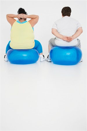 fat man exercising - Overweight man and woman Exercising on exercise Balls, back view Stock Photo - Premium Royalty-Free, Code: 693-03565336
