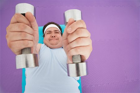 fat man exercising - Overweight Man lying down Lifting dumbbells, overhead view Stock Photo - Premium Royalty-Free, Code: 693-03565332