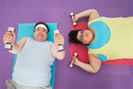 fat man exercising - Overweight man and woman lying down lifting dumbbells, overhead view Stock Photo - Premium Royalty-Free, Code: 693-03565333