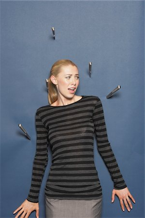 people in panic - Woman surrounded by thrown knives against blue background Stock Photo - Premium Royalty-Free, Code: 693-03565594