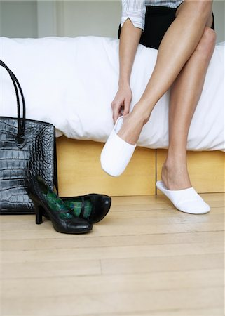 Young woman sitting on bed, putting on slippers, bag and shoes on floor, low section Stock Photo - Premium Royalty-Free, Code: 693-03565725