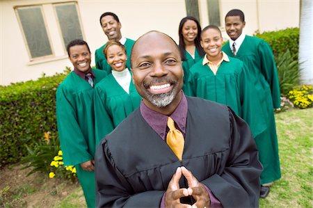 Minister in church garden, gospel choir in background, portrait Stock Photo - Premium Royalty-Free, Code: 693-03686354