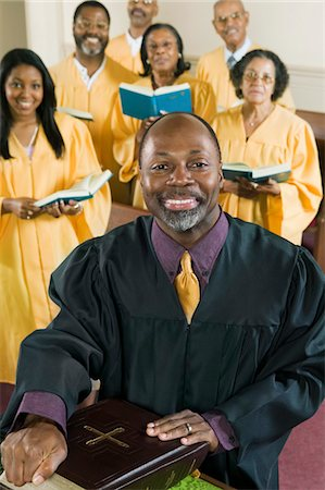Minister at altar with Bible, gospel choir in background, portrait Stock Photo - Premium Royalty-Free, Code: 693-03686352