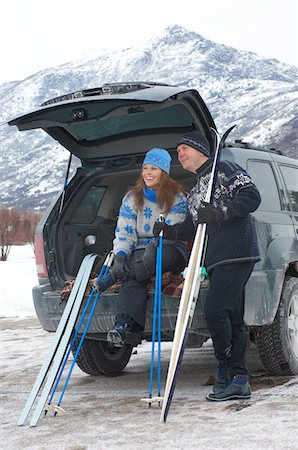 Couple relaxing at back of car, holding cross-country skis and poles in snow Stock Photo - Premium Royalty-Free, Code: 693-03707247