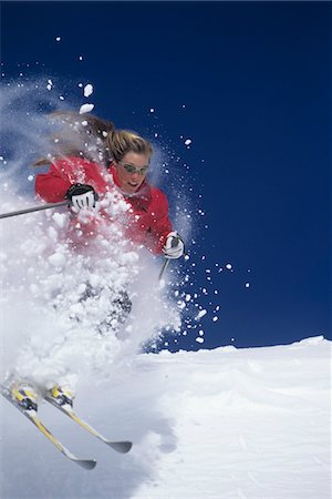Skier skiing through powdery snow on ski Slope Stock Photo - Premium Royalty-Free, Code: 693-03707729