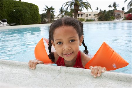 Girl (5-6 years) holding on to edge of swimming pool Stock Photo - Premium Royalty-Free, Code: 693-03707931