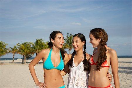 Three teenage girls (16-17) wearing bikinis, standing on beach, portrait Stock Photo - Premium Royalty-Free, Code: 693-03707944
