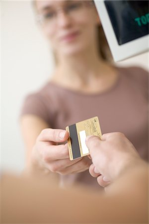 Lady passing over a debit/credit card Stock Photo - Premium Royalty-Free, Code: 693-03782636