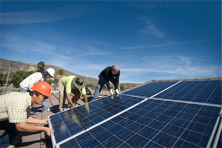 solar power - A group of men laying down a large solar panel Stock Photo - Premium Royalty-Free, Code: 693-03782708