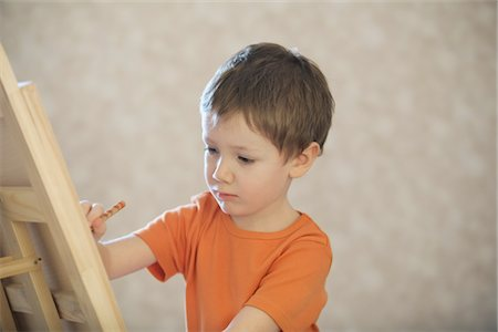 drawing (artwork) - A young boy drawing onto a canvas Stock Photo - Premium Royalty-Free, Code: 693-03782882