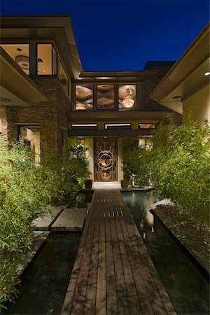 House exterior at night with wooden walkway over water Stock Photo - Premium Royalty-Free, Code: 693-03782971