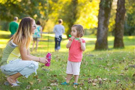 Little Girl and Woman Blowing Bubbles in Park Stock Photo - Rights-Managed, Code: 700-04931695