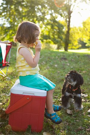 Girl Sitting on Cooler Eating Hamburger Stock Photo - Rights-Managed, Code: 700-04931691