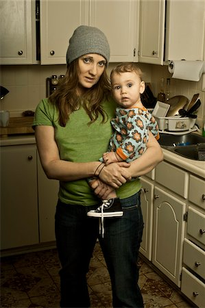 Mother Holding Son in Messy Kitchen Stock Photo - Rights-Managed, Code: 700-04981807