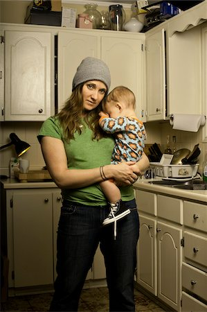 Mother Holding Son in Cluttered Kitchen Stock Photo - Rights-Managed, Code: 700-04981808