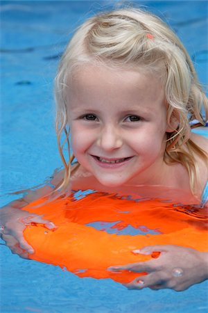 Girl Swimming with Orange Float in Swimming Pool Stock Photo - Rights-Managed, Code: 700-05450959