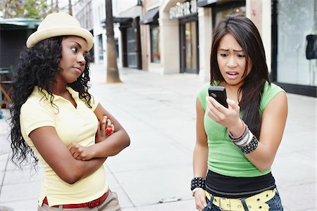 Woman with Cell Phone Looking Surprised While Friend Looks on Disapprovingly Stock Photo - Rights-Managed, Code: 700-05451004