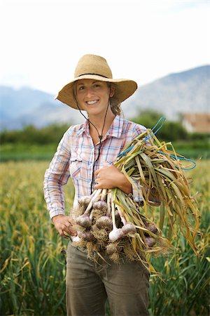farmhand (female) - Portrait Farmer Holding Armful of Garlic on Organic Farm Stock Photo - Rights-Managed, Code: 700-05602725