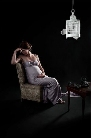 silk - Pregnant Woman Sitting on Chair in Room with Birdcage and Telephone Stock Photo - Rights-Managed, Code: 700-05653229