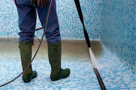 Close-Up of Man Cleaning Swimming Pool with Pressure Washer Stock Photo - Rights-Managed, Code: 700-05662377