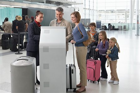 Airport Employee Helping Family Check In at Airport Stock Photo - Rights-Managed, Code: 700-05756419