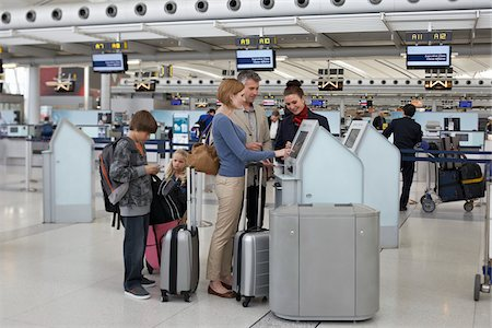 Employee Helping Family Check In at Airport Stock Photo - Rights-Managed, Code: 700-05756424