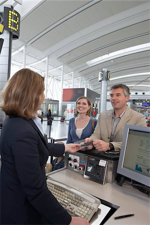 Couple at Ticket Counter in Airport Stock Photo - Rights-Managed, Code: 700-05756429