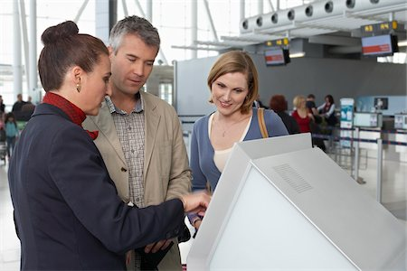 Employee Helping Couple Check In at Airport Stock Photo - Rights-Managed, Code: 700-05756420