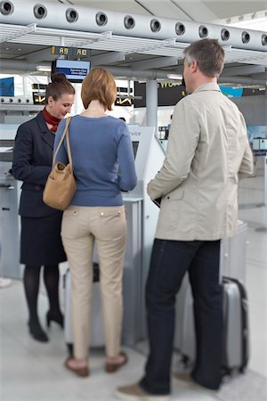 Employee Helping Couple Check In at Airport Stock Photo - Rights-Managed, Code: 700-05756422