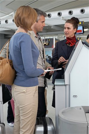 Employee Helping Couple Check In at Airport Stock Photo - Rights-Managed, Code: 700-05756423