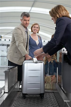 Family Checking Luggage at Airport Stock Photo - Rights-Managed, Code: 700-05756431