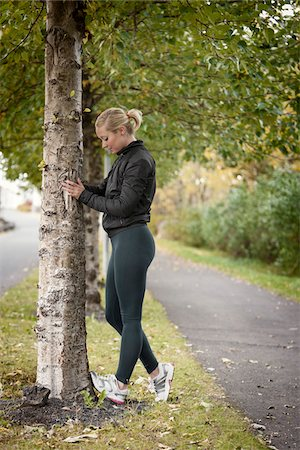 Jogger Stretching Calves Against Tree Stock Photo - Rights-Managed, Code: 700-05762106