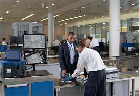 rear - Security Guard Checking Businessman's Luggage in Airport Stock Photo - Rights-Managed, Code: 700-05821740