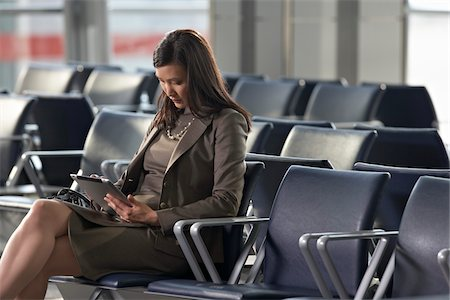 Businesswoman Using Tablet Computer in Airport Stock Photo - Rights-Managed, Code: 700-05821766