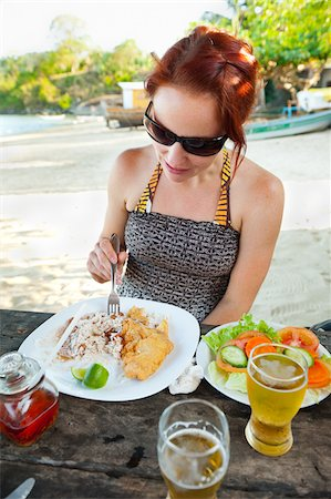 Woman Eating Meal of Fried Fish, Rice and Beans, and Salad at Beachside Cafe, near Paraty, Rio de Janeiro, Brazil Stock Photo - Rights-Managed, Code: 700-05947867