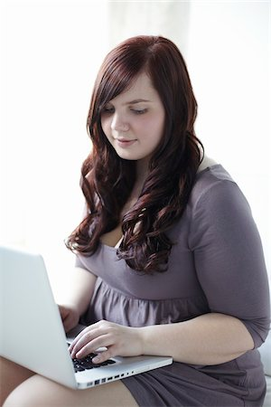 fat lady sitting - Woman Typing on Laptop Stock Photo - Rights-Managed, Code: 700-06144791
