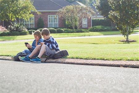 Two Boys Sitting on Neighbourhood Curb with Handheld Electronics Stock Photo - Rights-Managed, Code: 700-06439139
