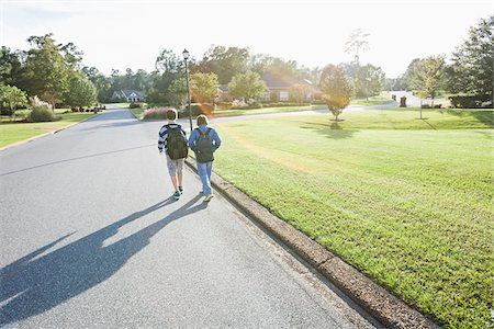 Two Boys Wearing Knapsacks and Walking through Neighbourhood on Way to School Stock Photo - Rights-Managed, Code: 700-06439145