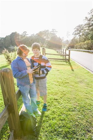Two Boys with Tablet Computer Standing Outdoors near Roadside Fence Stock Photo - Rights-Managed, Code: 700-06439149