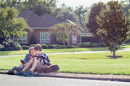 Two Boys Sitting on Neighbourhood Curb with Handheld Electronics Stock Photo - Rights-Managed, Code: 700-06439140