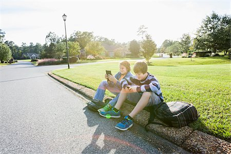 Two Boys Sitting on Neighbourhood Curb with Handheld Electronics Stock Photo - Rights-Managed, Code: 700-06439142