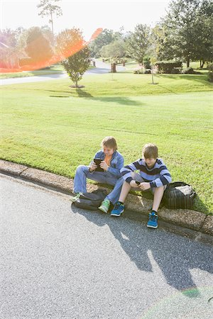 Two Boys Sitting on Neighbourhood Curb with Handheld Electronics Stock Photo - Rights-Managed, Code: 700-06439143
