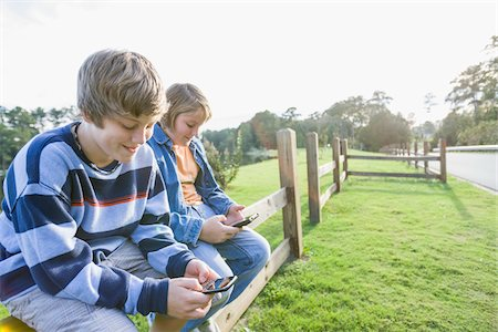 Two Boys with Handheld Electronics Sitting on Roadside Fence Stock Photo - Rights-Managed, Code: 700-06439150