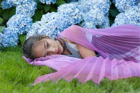 Girl Wearing Fairy Wings Lying Down Outside in Flower Garden Stock Photo - Rights-Managed, Code: 700-06431493