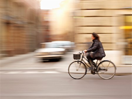 Woman riding bicycle through town, Tuscany, Italy Stock Photo - Rights-Managed, Code: 700-06452091