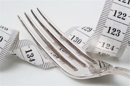 Close-Up of Fork Lying on top of Measuring Tape Stock Photo - Rights-Managed, Code: 700-06465381