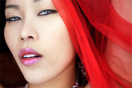 Close up of face of young woman wearing red scarf, looking at camera, Bangkok, Thailand Stock Photo - Rights-Managed, Code: 700-06531688