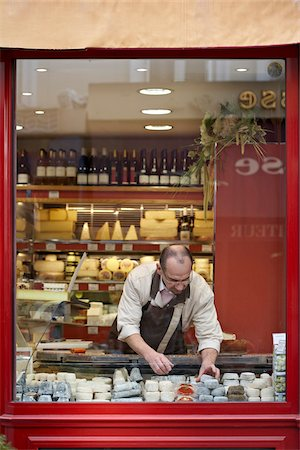 french - male shopkeeper arranging fresh wedges and rounds of French goat cheese in artisan cheese shop window, La Fromagerie, Paris, France Stock Photo - Rights-Managed, Code: 700-06531951