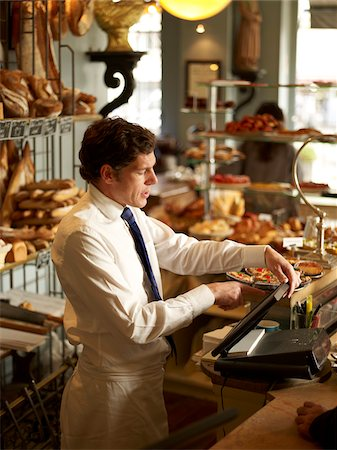 Waiter in Wearing Shirt, Tie, and Apron Operating Cash Machine in Bakery, Paris, France Stock Photo - Rights-Managed, Code: 700-06531976